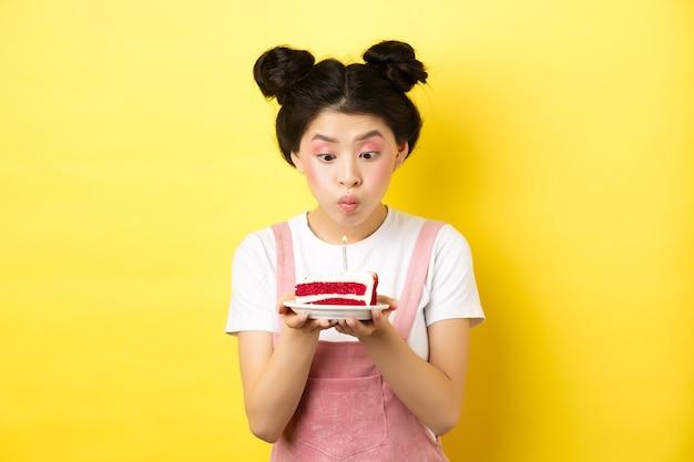 Feiertage und feier. dumme asiatische mädchen mit glamour make-up, wunsch machen und kerze auf geburtstagstorte blasen, auf gelb stehen.