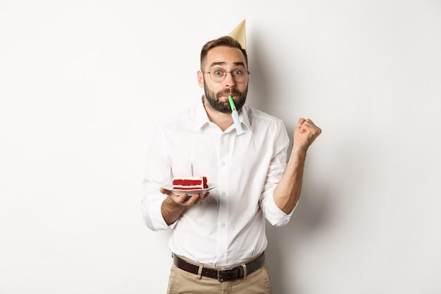 Feiertage und feier. fröhlicher mann, der geburtstag genießt, partypfeife bläst und bday kuchen, weißer hintergrund hält.