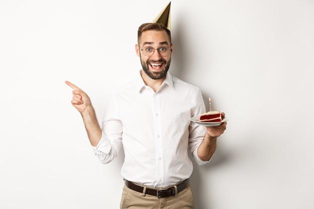 Feiertage und feier. glücklicher mann, der geburtstagsfeier genießt, bday kuchen hält und finger links auf promo zeigt, stehend