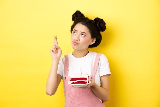 Feiertage und feier. nettes asiatisches geburtstagskind, das wunsch an partei wünscht kuchen und kerze, daumen kreuzen und nach oben schauen, auf gelb stehend