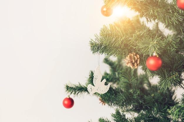 Feiertage und feierkonzept - geschmückter weihnachtsbaum auf weißem hintergrund mit exemplar
