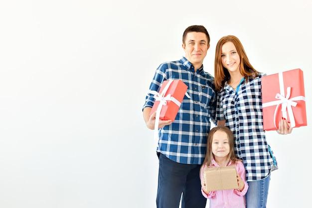 Feiertage und feierkonzept - glückliche familie mit weihnachtsgeschenken auf weißem hintergrund mit kopienraum
