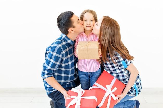 Feiertage und feierkonzept - glückliche familie mit weihnachtsgeschenken auf weißem hintergrund.