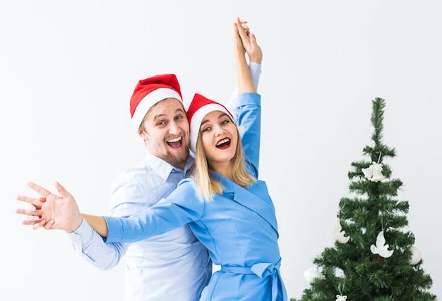Feiertage und feierkonzept - junges lustiges paar, das weihnachten zu hause feiert