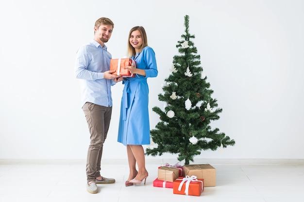 Feiertage und feierkonzept - mann, der seiner freundin ein weihnachtsgeschenk gibt.