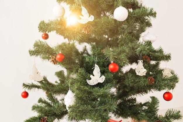 Feiertage und feierkonzept - nahaufnahme des geschmückten weihnachtsbaums auf weißem hintergrund
