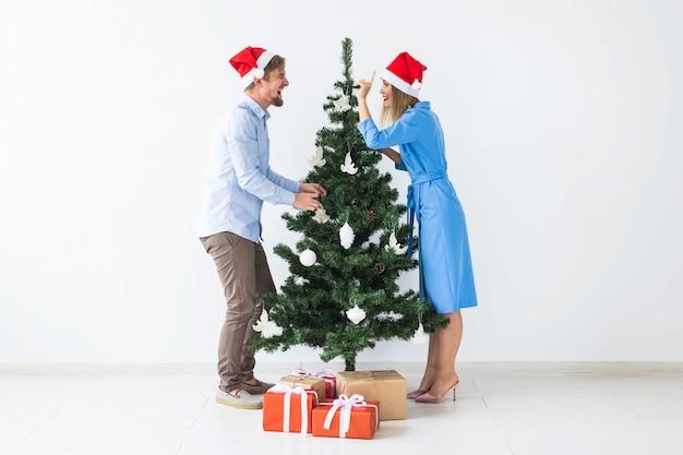Feiertage und festliches konzept - junges familienpaar in weihnachtsmützen, die den weihnachtsbaum schmücken