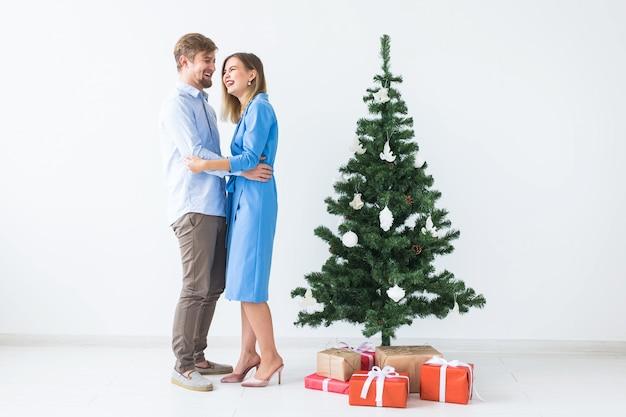Feiertage und festliches konzept - junges glückliches paar nahe einem weihnachtsbaum auf weißem hintergrund.