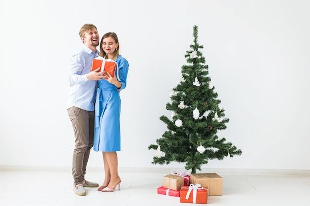 Feiertage und festliches konzept - junges glückliches paar nahe einem weihnachtsbaum auf weißem raum