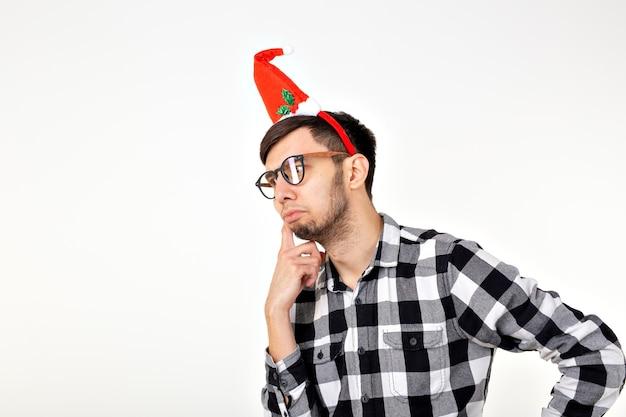 Feiertage und geschenke konzept - lustiger emotionaler mann in weihnachtsmütze auf weißem hintergrund mit exemplar