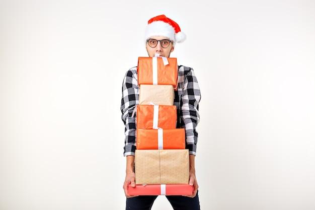Feiertage und geschenke konzept - lustiger mann in weihnachtsmütze hält viele geschenkboxen auf weißem hintergrund mit exemplar