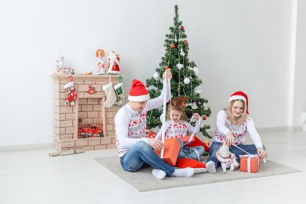 Feiertage und geschenkkonzept - porträt einer glücklichen familie, die zur weihnachtszeit geschenke öffnet.