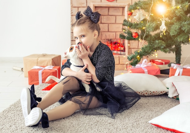 Feiertage und kindheitskonzept - porträt des kleinen glücklichen netten kindermädchens und des welpen mit weihnachtsgeschenk.