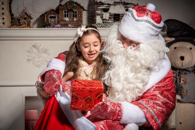 Feiertage und leutekonzept - lächelndes kleines mädchen mit weihnachtsmann