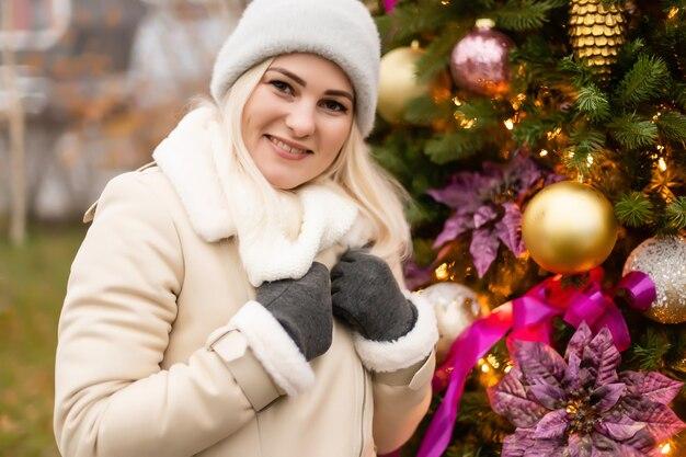 Feiertage und leutekonzept - schöne glückliche junge frau über weihnachtsbaumlichtern am winterabend