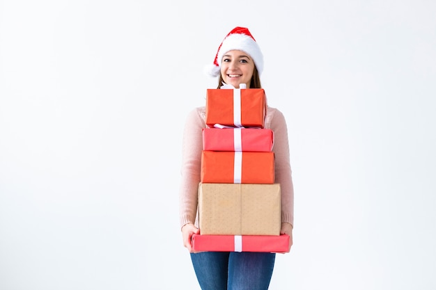 Feiertage und leutekonzept - weihnachtssanta-fraueneinkaufen, die viele geschenke tragen, die sankt-hut tragen, der glücklich auf weißem hintergrund mit kopienraum lächelt.