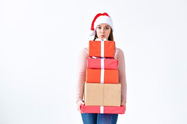 Feiertage und leutekonzept - weihnachtssanta-fraueneinkaufen, die viele geschenke tragen, die sankt-hut tragen, der glücklich auf weißem hintergrund mit kopienraum lächelt. Premium Fotos