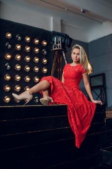 Feiertage und modekonzept - schöne sexy frau im roten kleid über lichthintergrund