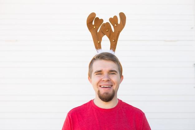 Feiertage und weihnachtskonzept - junger glücklicher mann in den hörnern des hirsches auf weißem hintergrund.