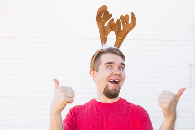 Feiertage und weihnachtskonzept - junger mann in hirschhörnern mit daumen nach oben geste auf weißem hintergrund.