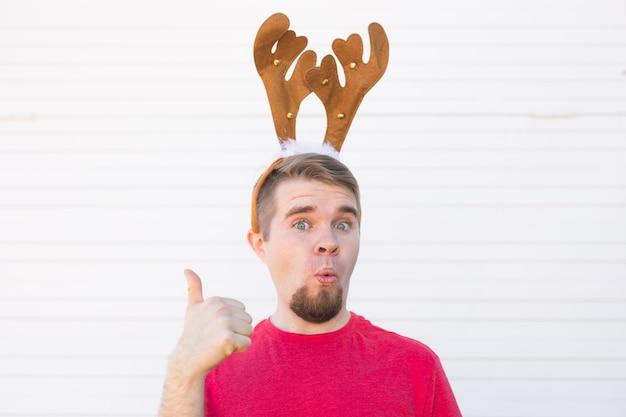 Feiertage und weihnachtskonzept - junger überraschter mann in hirschhörnern mit daumen nach oben geste auf weißem hintergrund