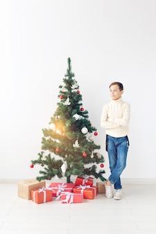 Feiertage und winterkindheitskonzept - lächelnder jugendlich junge, der nahe weihnachtsbaum auf weißem hintergrund steht.