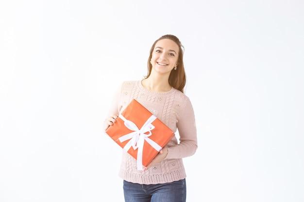 Feiertage, valentinstag und festliches konzept - schöne lächelnde frau mit langen haaren, die geschenkbox hält. weißer hintergrund isoliert studioportrait, exemplar