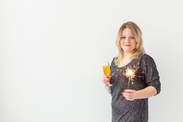Feiertage, weihnachten, geburtstag und neujahrskonzept - frau feiert und hält wein in einem glas und einer wunderkerze auf weißem hintergrund mit kopierraum
