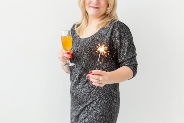 Feiertage, weihnachten, geburtstag und neujahrskonzept - frau feiert und hält wein in einem glas und einer wunderkerze auf weißem hintergrund, nahaufnahme Premium Fotos