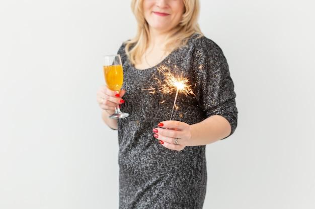 Feiertage, weihnachten, geburtstag und neujahrskonzept - frau feiert und hält wein in einem glas und einer wunderkerze auf weißem hintergrund, nahaufnahme