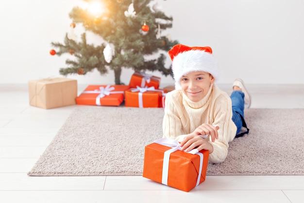 Feiertage, weihnachten, kindheit und leutekonzept - lächelnder glücklicher jugendlich junge in sankt-hut öffnet geschenkbox über weihnachtsbaumhintergrund.