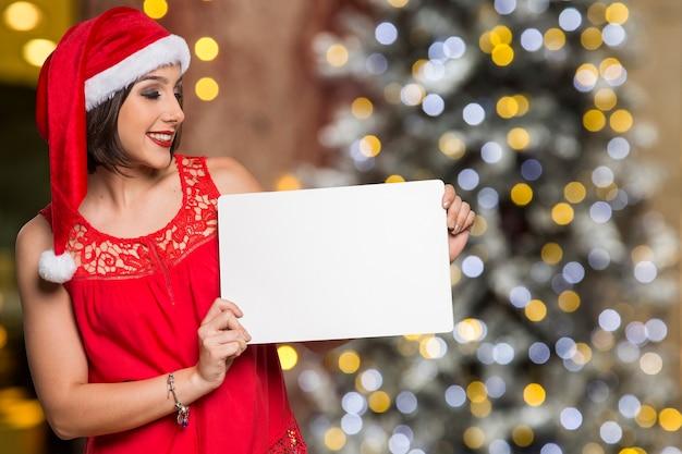 Feiertage, weihnachten. porträt der lächelnden frau, die die weihnachtsmütze trägt, die leeres plakat über bokeh weihnachtslichtern zeigt
