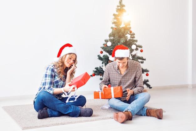 Feiertage, weihnachten und familienkonzept - junges glückliches paar, das zu hause geschenke öffnet.