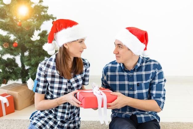 Feiertage, weihnachten und familienkonzept - liebevolles glückliches paar, das geschenke zu hause öffnet