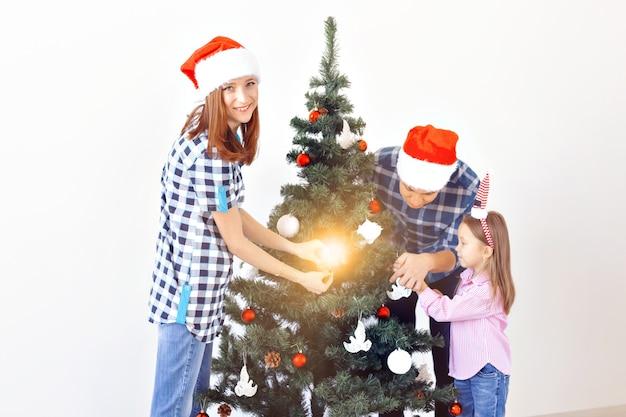 Feiertage, weihnachten und feierndes konzept - glückliche familie, die weihnachtsbaum im feiertag auf weißem hintergrund verziert.