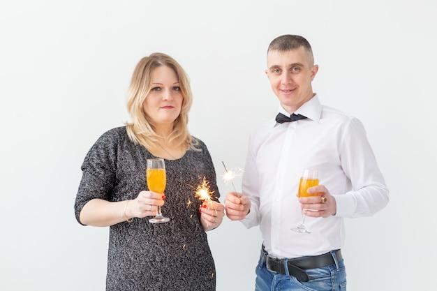 Feiertage, weihnachten, valentinstag und neujahrskonzept - frau und mann feiern und halten wein in einem glas auf weißem hintergrund.