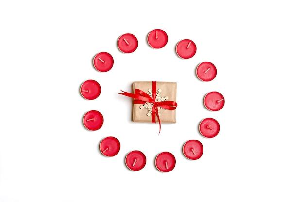 Feiertage, winter und feierkonzept - weihnachtszusammensetzung. kerzen, geschenk, weißes bac