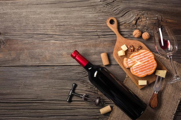 Feiertags-abendesseneinstellung mit rotwein und frischkäse auf rustikalem holz. draufsicht mit platz für ihre grüße.