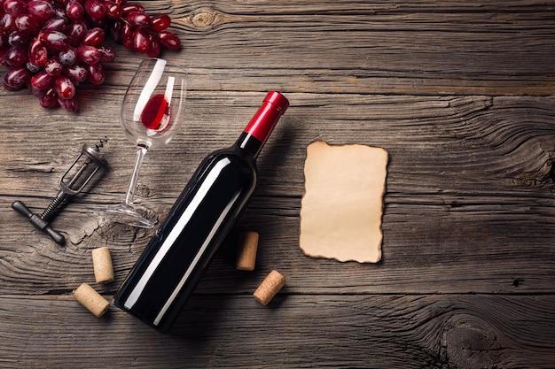 Feiertags-abendesseneinstellung mit rotwein und geschenk auf rustikalem holz. draufsicht mit platz für ihre grüße.