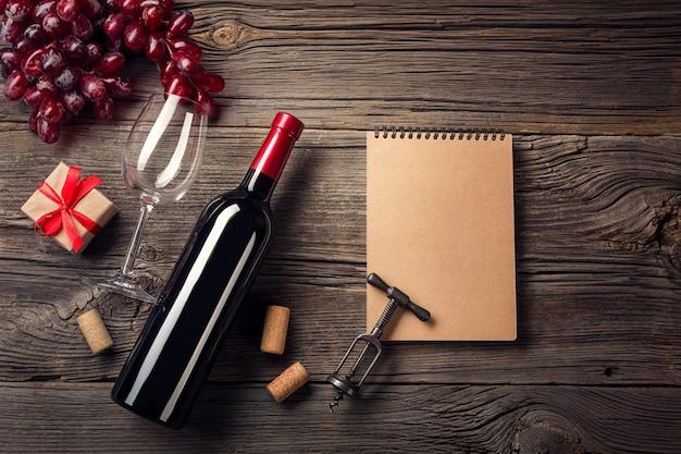 Feiertags-abendesseneinstellung mit rotwein und geschenk auf rustikalem holz in der flachen lageansicht.