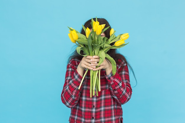 Feiertags-, blumen- und personenkonzept - lustiges mädchen im karierten hemd mit blumenstrauß-tulpen in den händen, die auf einer blauen wand aufwerfen.