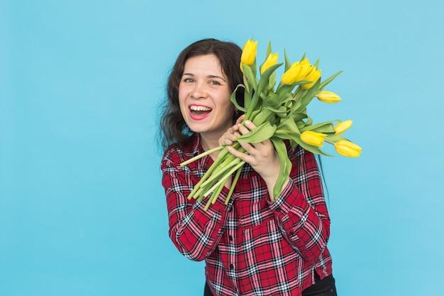 Feiertags-, blumen- und personenkonzept - lustiges mädchen im karierten hemd mit blumenstrauß-tulpen in den händen, die aufwerfen
