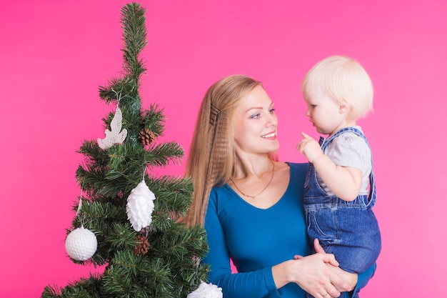 Feiertags-, familien- und weihnachtskonzept - junge frau mit ihrem baby nahe weihnachtsbaum auf rosa hintergrund