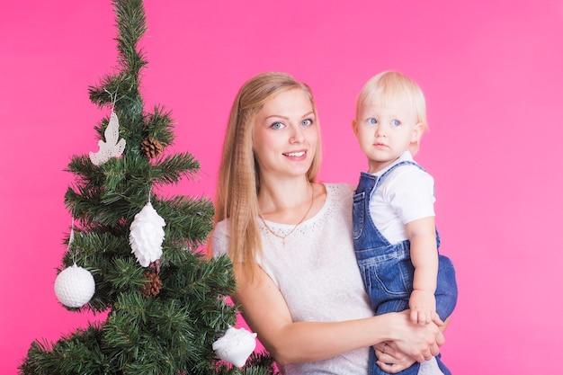 Feiertags-, familien- und weihnachtskonzept - junge mutter mit ihrer kleinen tochter nahe weihnachtsbaum auf