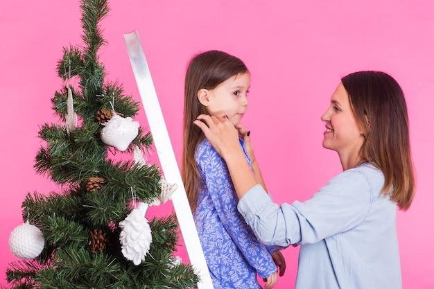 Feiertags-, familien- und weihnachtskonzept - mutter und tochter, die weihnachtsbaum auf rosa verzieren