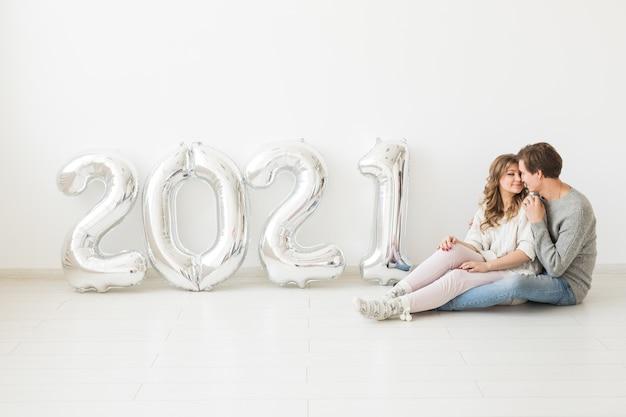 Feiertags-, fest- und partykonzept - glückliches liebespaar hält silberne 2021 luftballons auf weiß