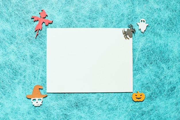Feiertags-halloween auf einem spinnennetzhintergrund mit einem weißen blatt, kürbis, geist, vogelscheuche, schädel, hexe