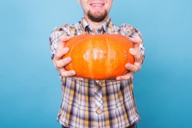 Feiertags-halloween- und people-konzept nahaufnahme eines großen orangefarbenen kürbisses in den händen eines mannes auf einem