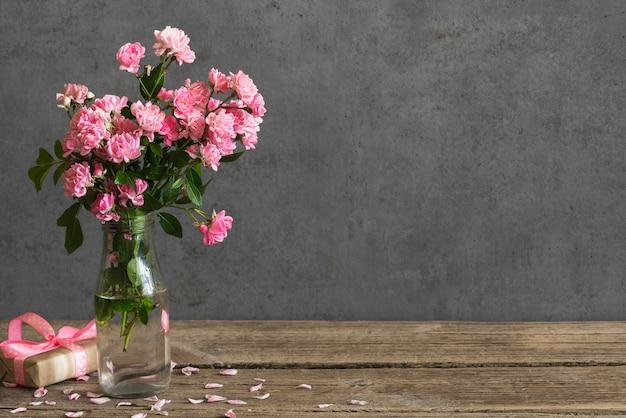 Feiertags- oder hochzeitskarte. stillleben mit rosa rosenblumenstrauß und geschenkbox.