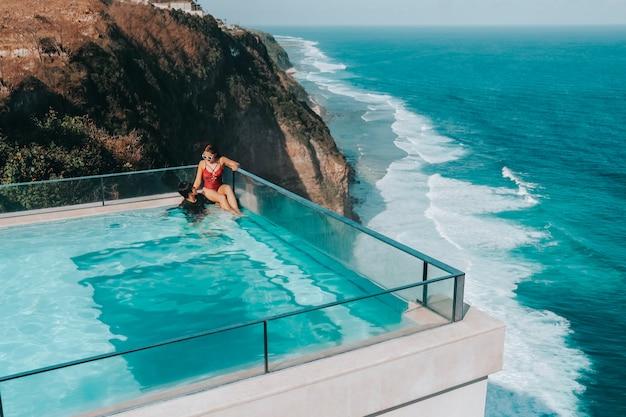Feiertags-paare, die im luxus mit luxuriösem swimmingpool des tropischen wasserlandhaus-erholungsortes mit meerblick bali, indonesien sich entspannen